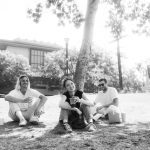 Photo shows Neil Frances duo sit with the singer on grass on a very sunny day.
