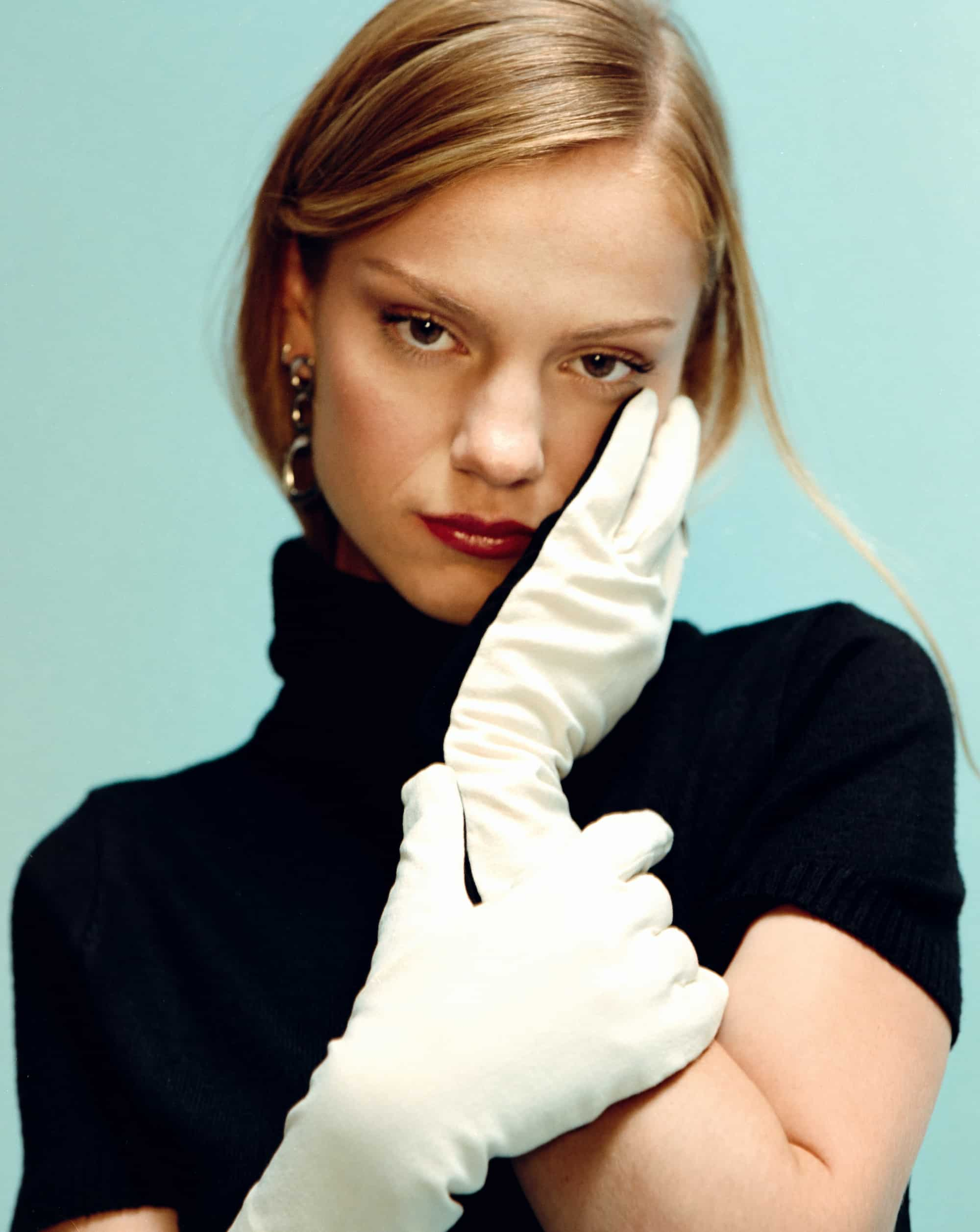 Amilli is posing with white gloves and a black dress, one of her hands is on her shin, the other is holding her wrist. She is wearing back in a light blue background, her face looks sexy but also serious, like a real deal!