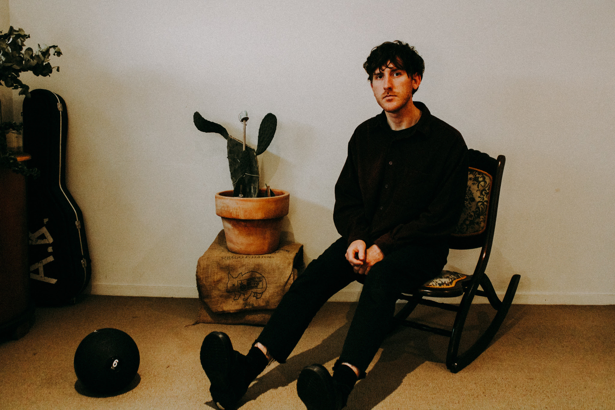Alexander is sitted on a dark wood chair, looking at the camera. Behind him there's a beige wall with a vase inside a vase and a cactus shaped plant. He is wearing black and has high boots and a gentle face.