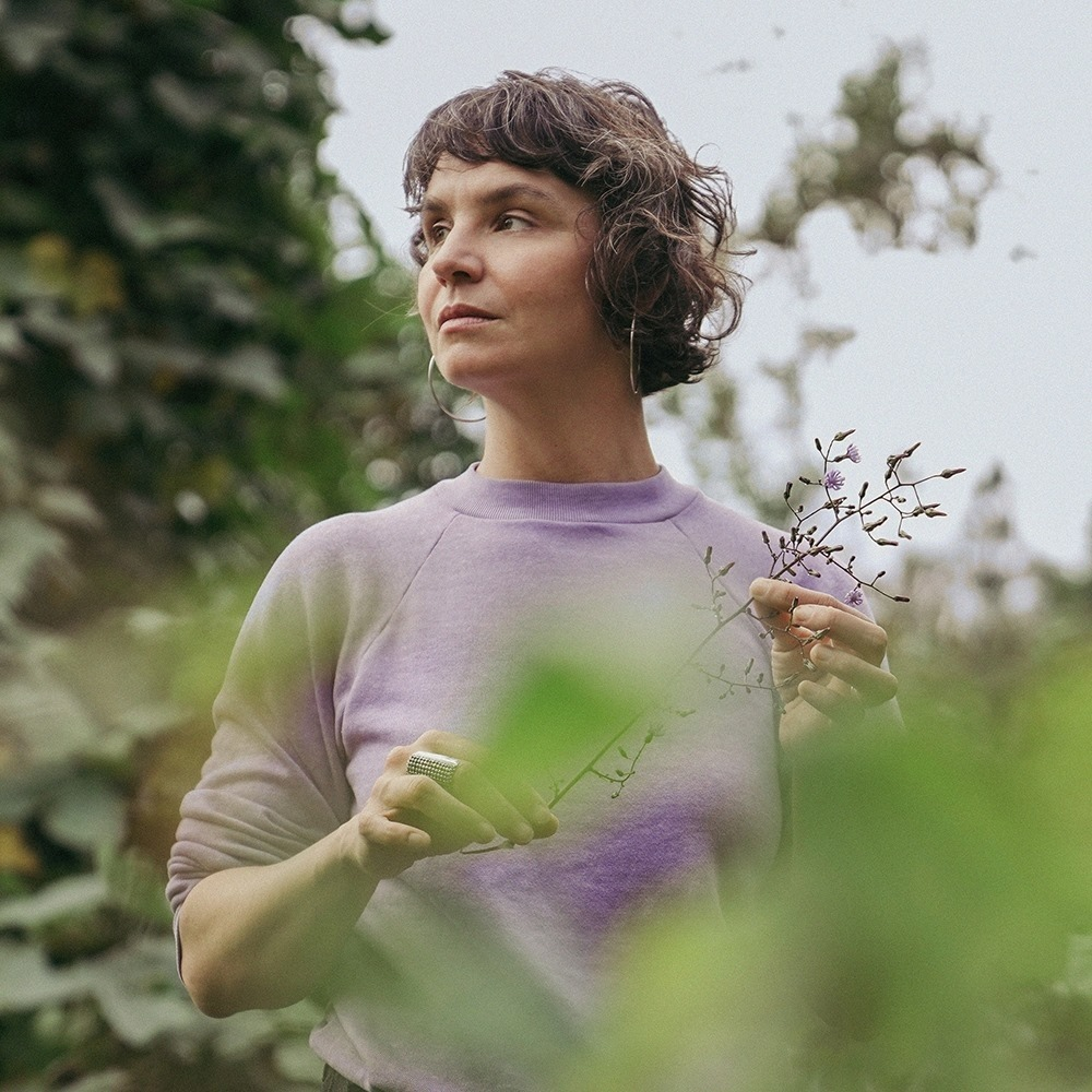 Kelly MacFarling is standing up, her hands are holding flowers, she wears a pink blouse. She is turning her head looking at a view, looking serious but in peace.
