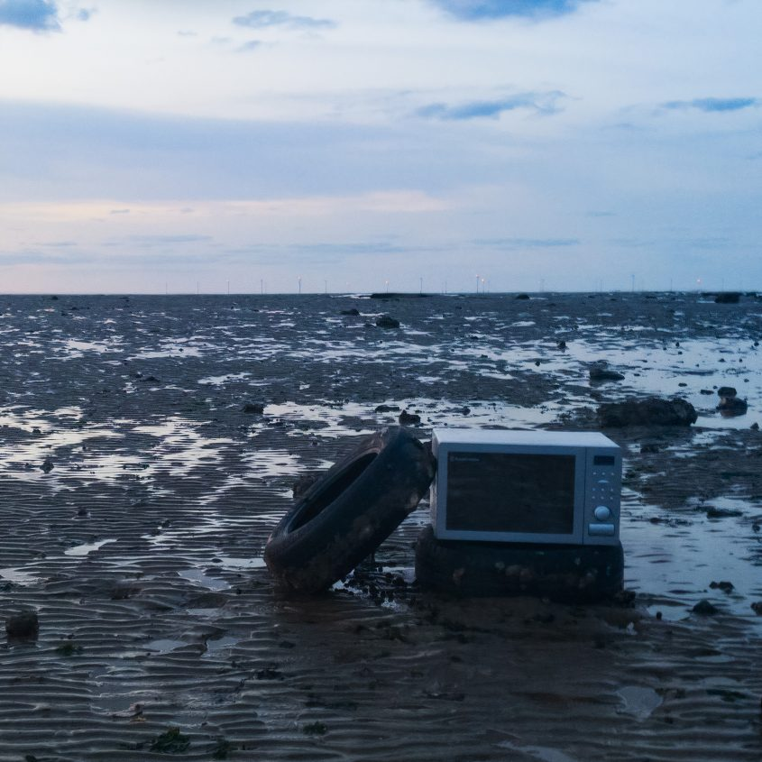 The imagem shows a muddy grownd with a tv and a tire supporting each other