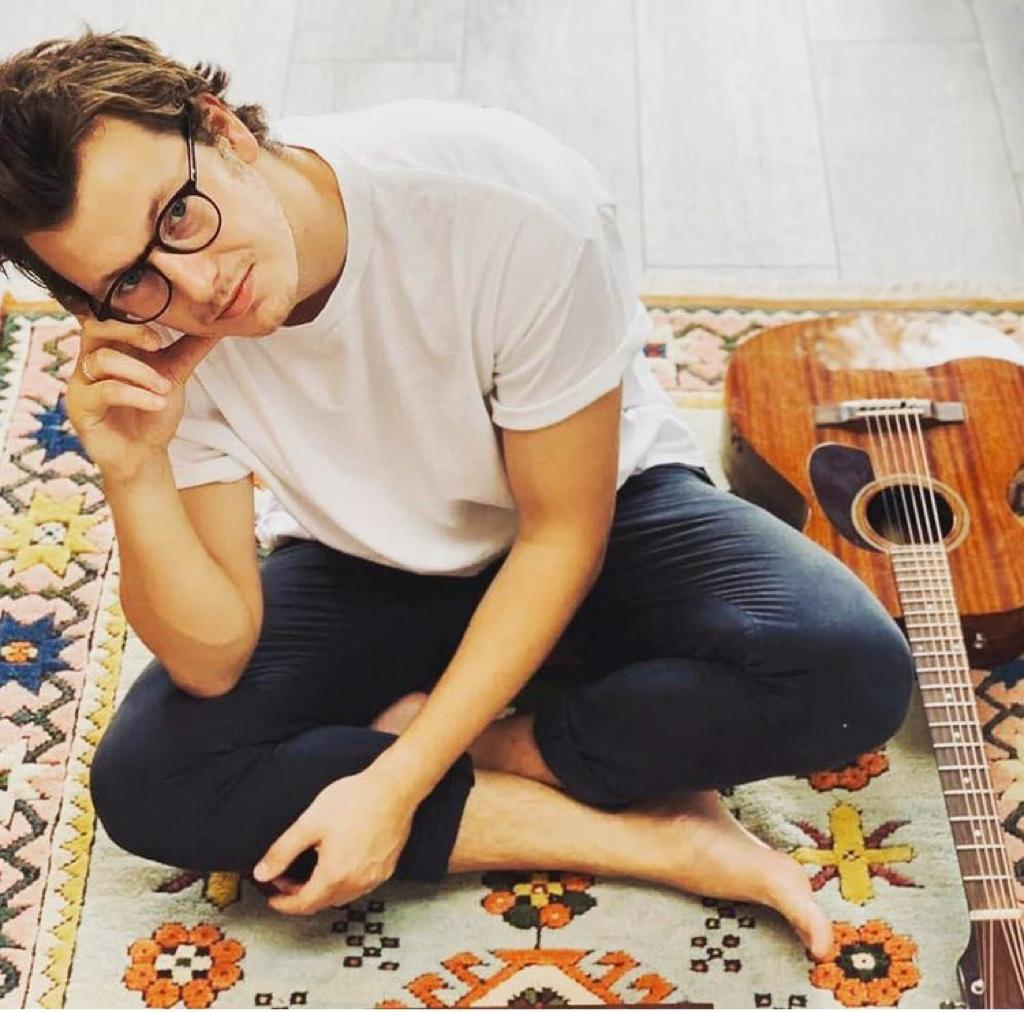 The photo shows the artist seated on the floor with the guitar by his side. He wears glasses and is looking at the camera.